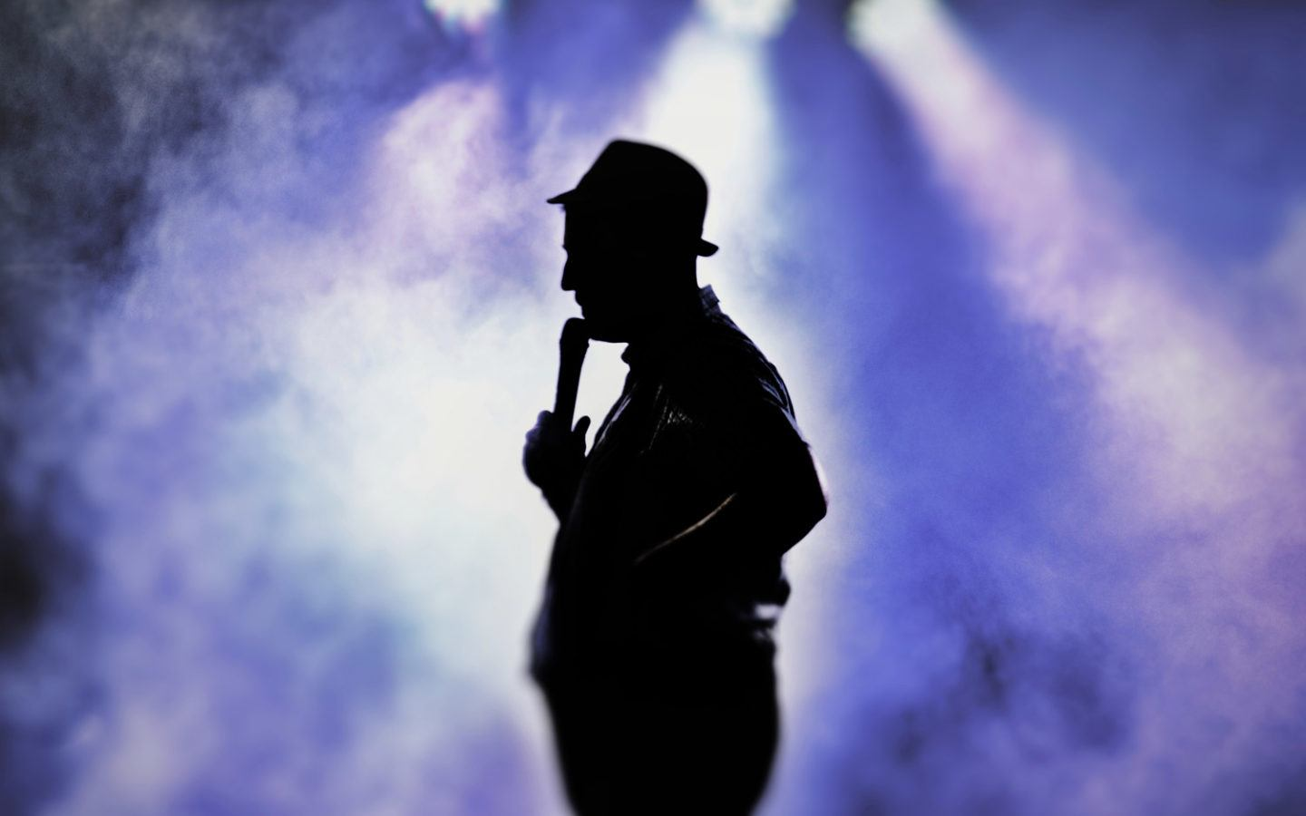 silhouette photo of man holding microphone