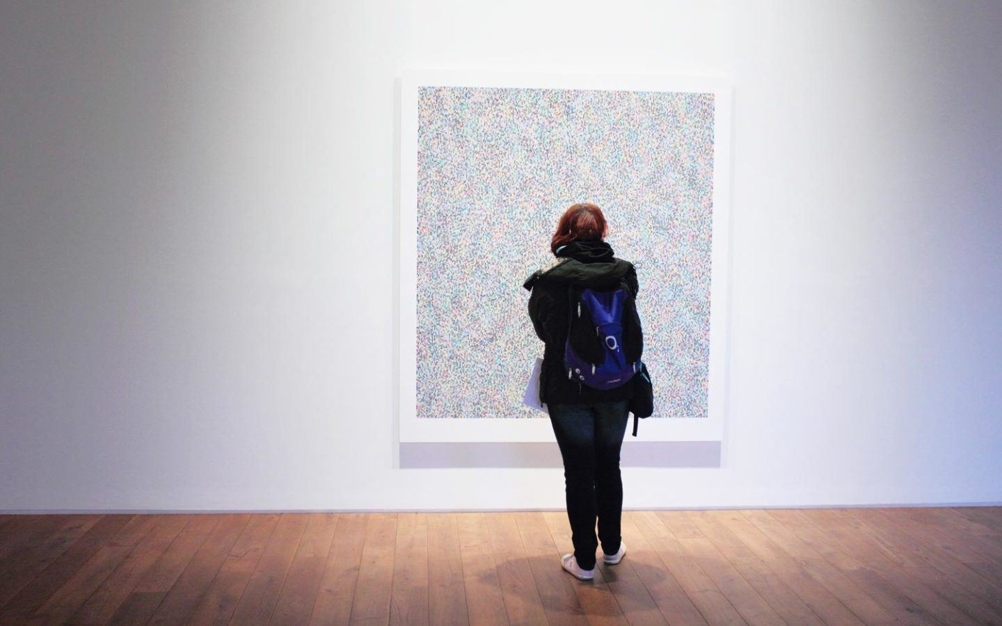 person in black jacket standing in front of art in museum