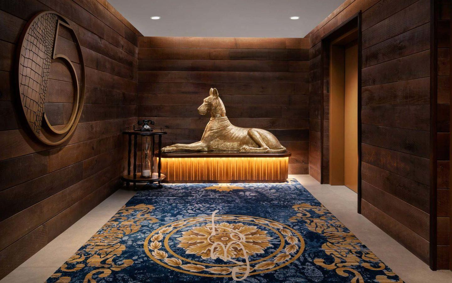 a stature of a large sitting dog in front of the elevators in a luxury hotel lobby