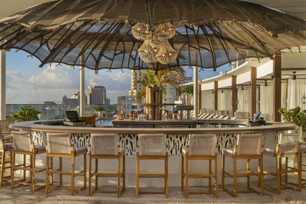 outdoor bar with chairs covered by a large decorative umbrella