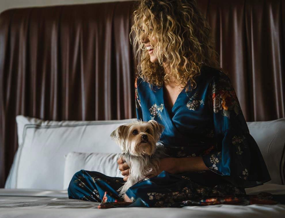 dog and woman with dirty blonde curly hair sitting on bed with white sheets and pillows