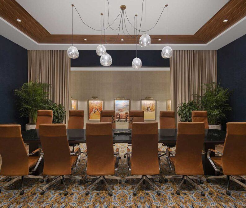 boardroom with long table and tall chairs below a light fixture