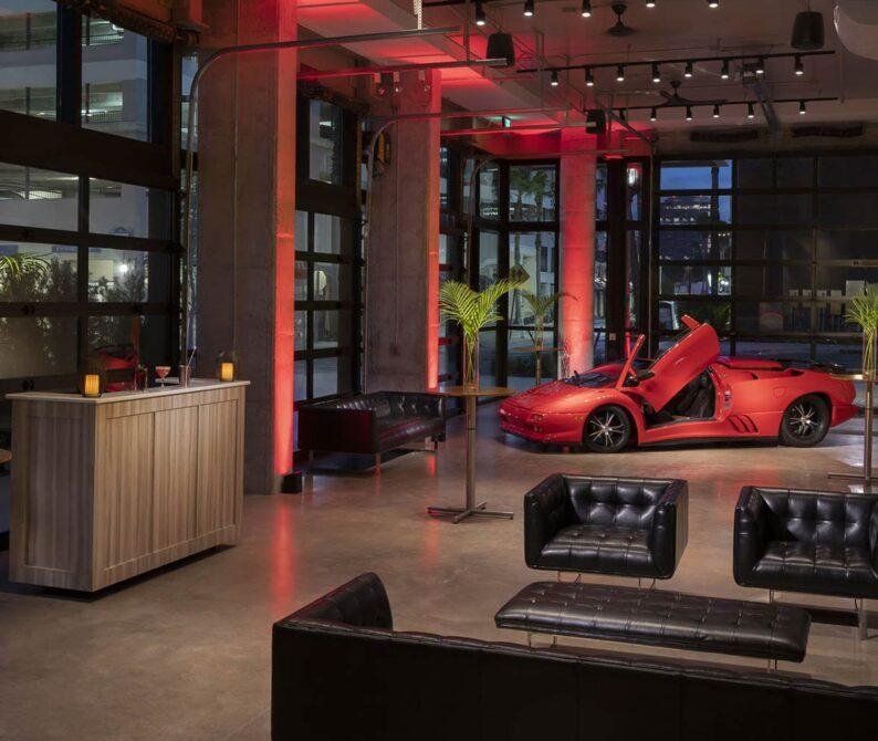 red luxury sports car in studio space with black leather chairs