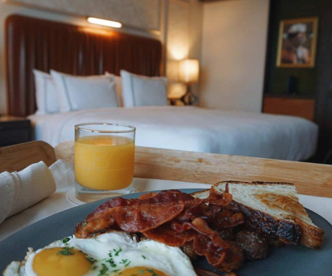 bacon eggs and orange juice on table in front of bed in hotel room