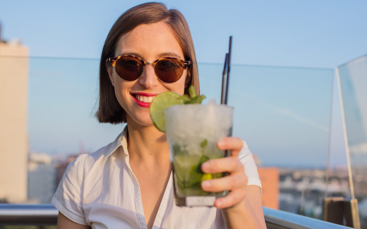 woman in white shirt holding up a mojito drink