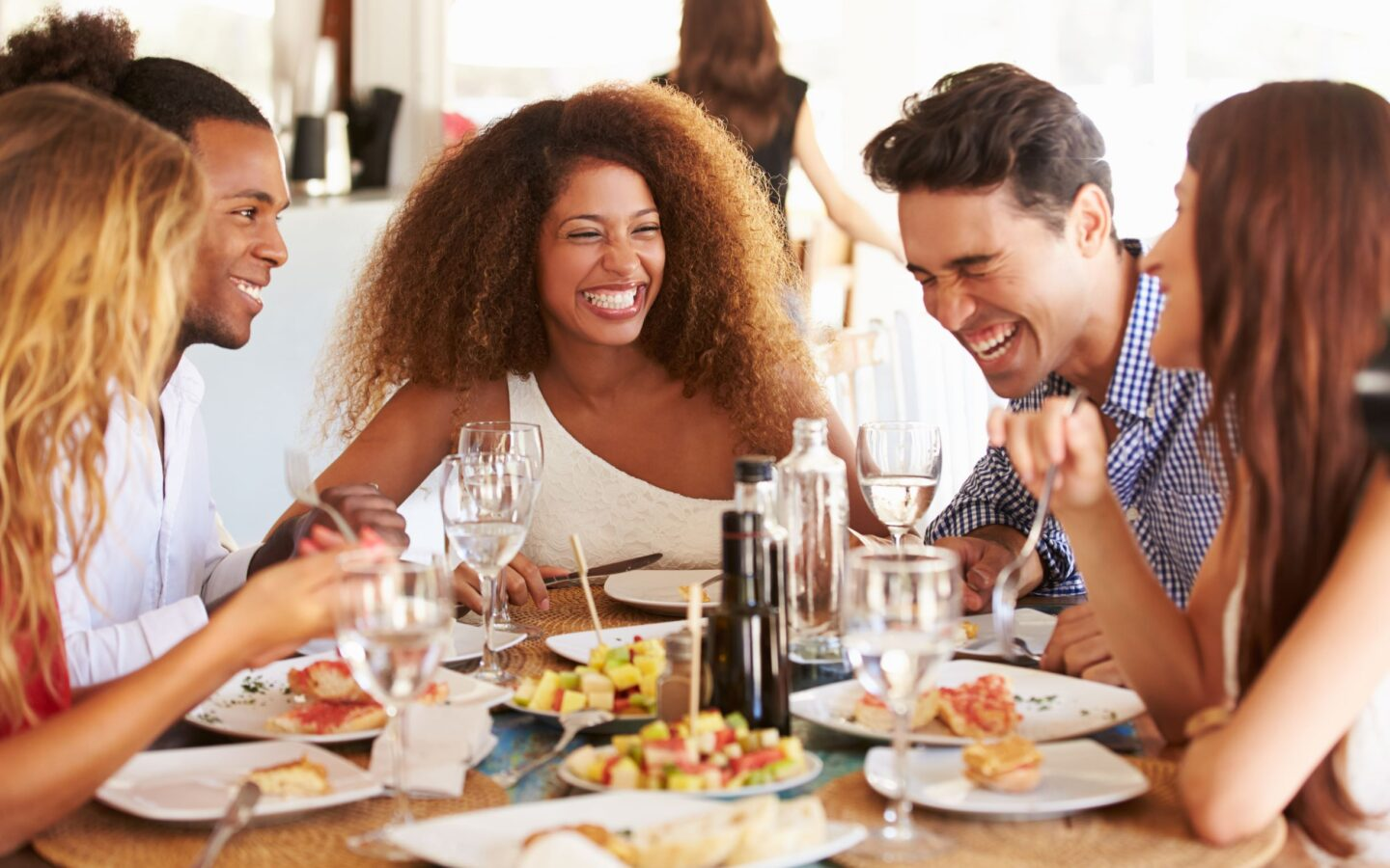 people sitting and laughing at a dinner table