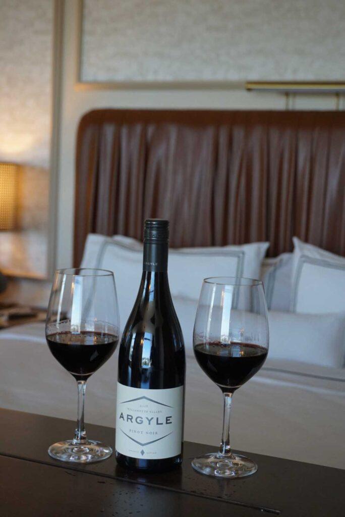 two wine bottles beside wine glass on table