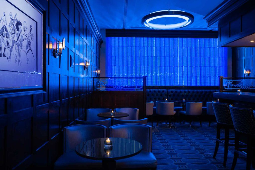 blue room interior of the Blue Bar with bar seating, and table seating