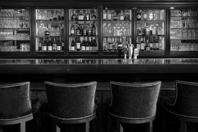 four black padded chairs at a bar
