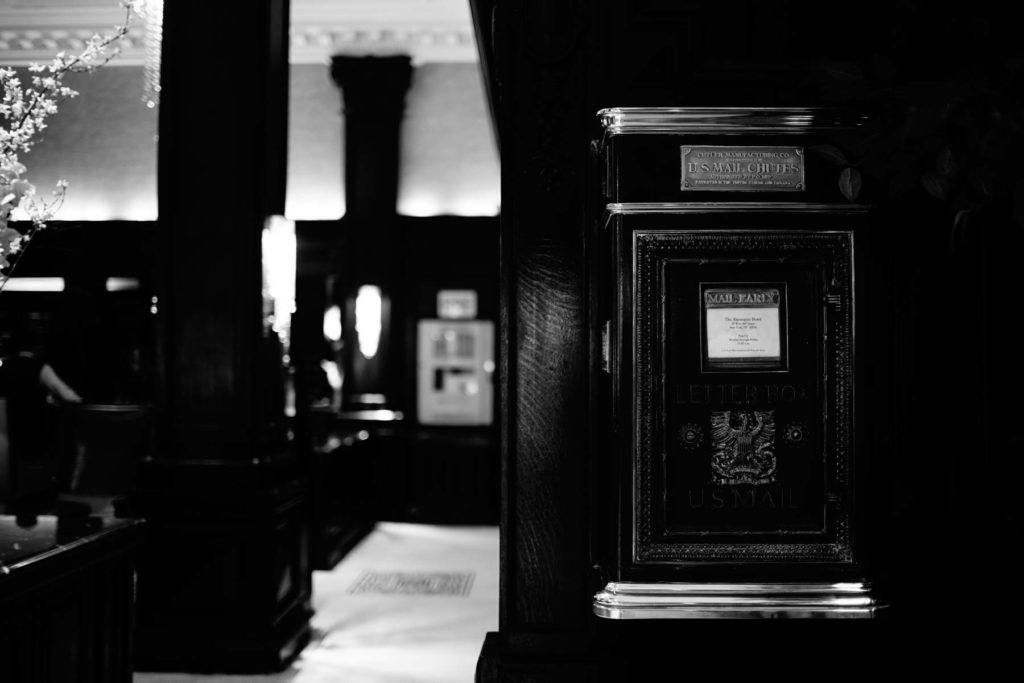 black and white photo old mailbox mounted on wall