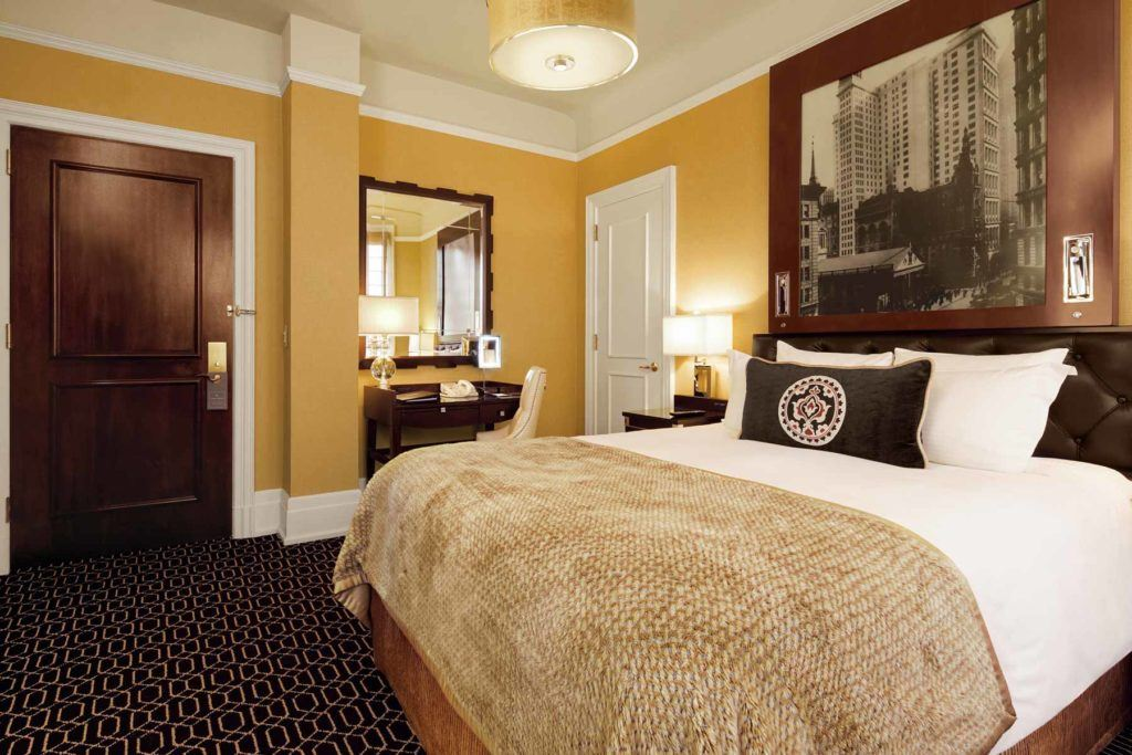 white and brown comforters on bed with painting on wall
