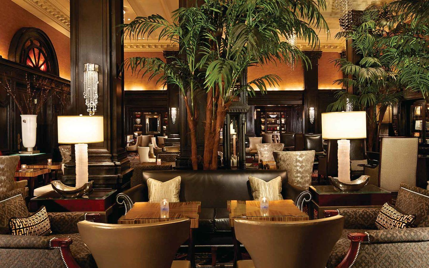 black leather sofa and arm chairs in the lobby lounge amongst green foliage