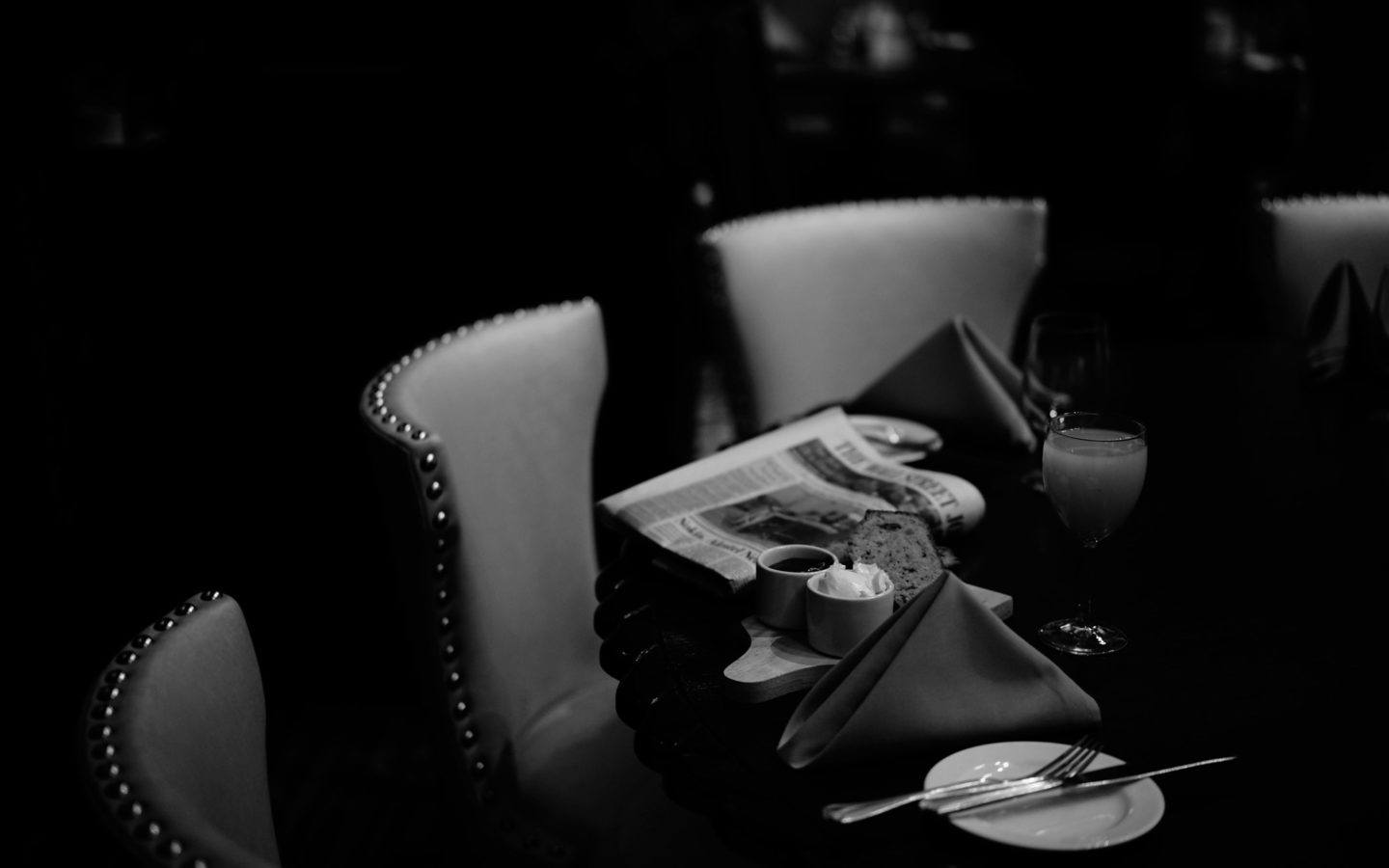 greyscale table setting of banana bread and the daily news paper