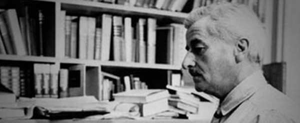 grayscale photo of William Faulkner standing in front of bookcase