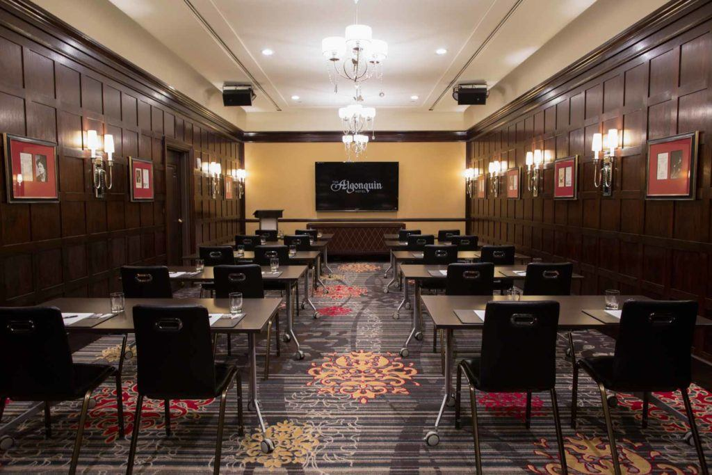 a luxurious hotel meeting room set with tables and chairs for a presentation