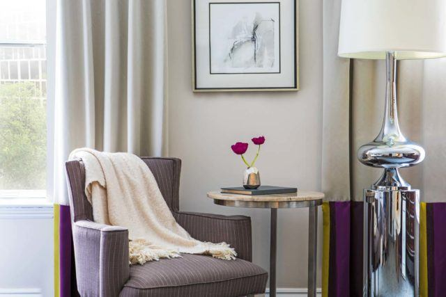 soft armchair with throw blanket and flowers on side table
