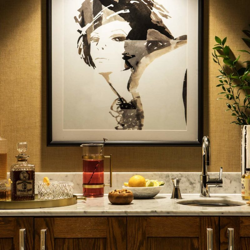 painting of woman's portrait on wall above mini bar
