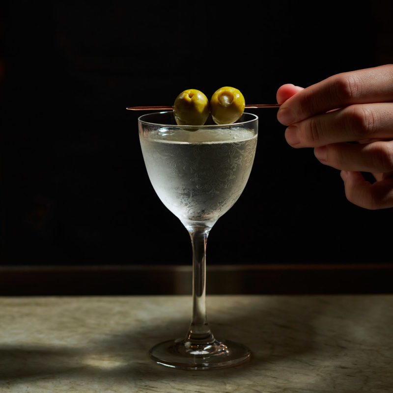 cocktail in long stemmed glass garnished with two olives