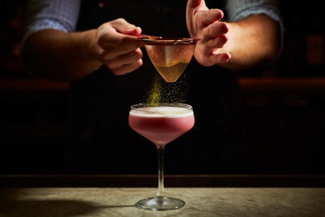 clear cocktail glass and bartender adding sprinkled garnish