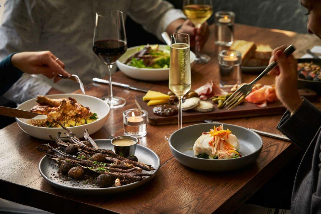 an array of dishes with dinner foods across a table