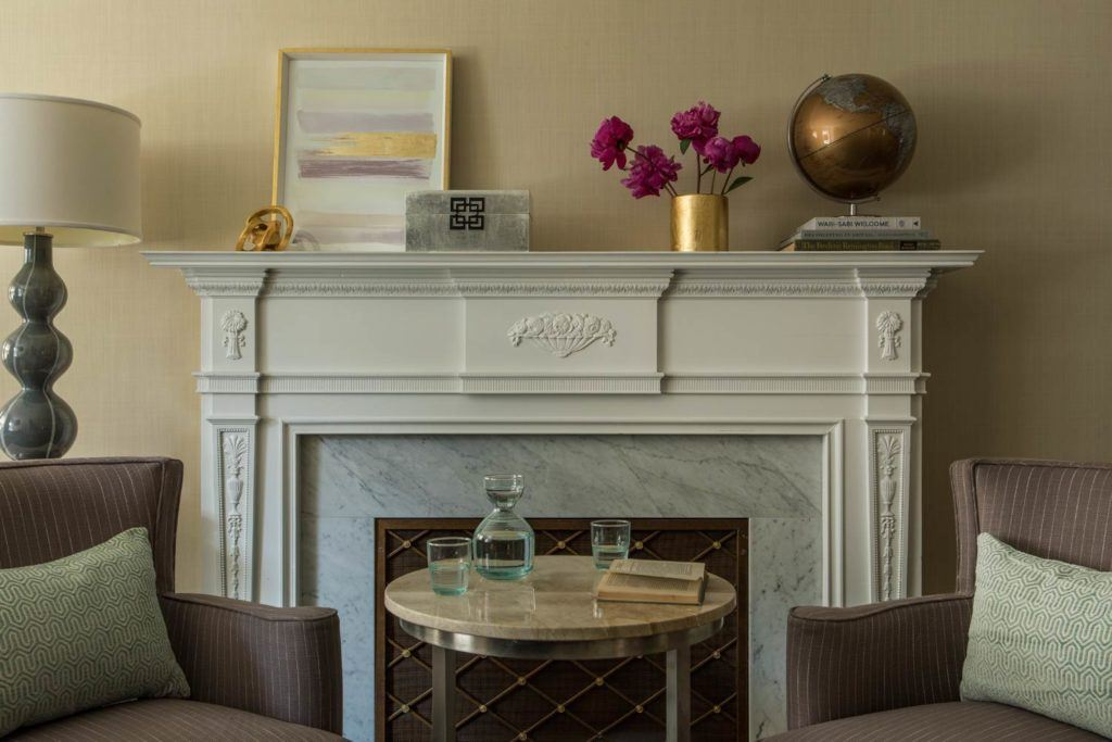 white fireplace mantle decorated with flowers, artwork and gold accents