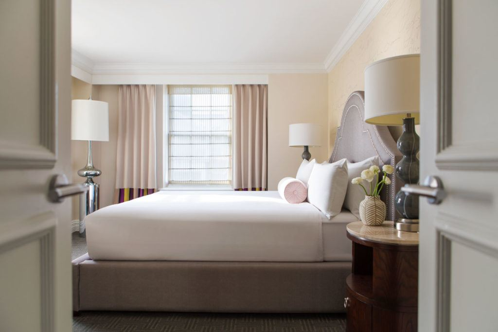 white mattress and brown bed frame next to large window