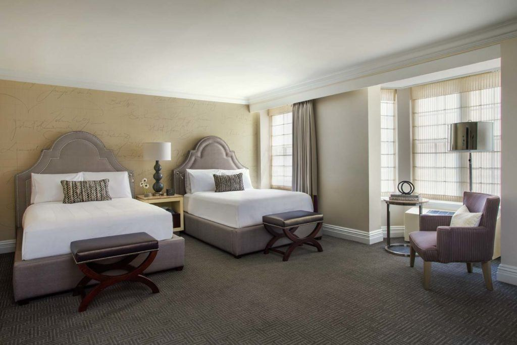 two beds in guest room with large windows
