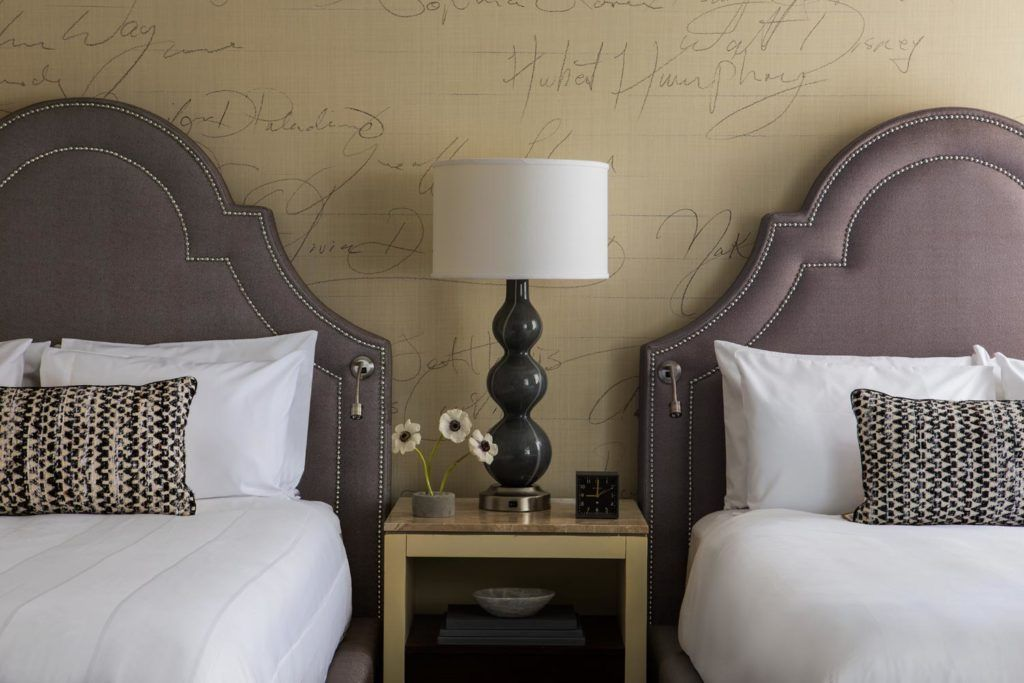 two beds with night table between them with table lamp