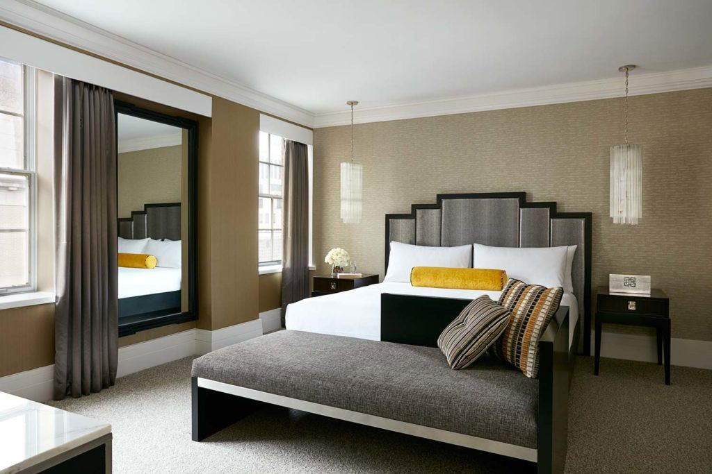 A luxury hotel suite bedroom with a large neatly made bed