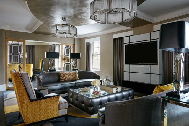 turned-off black flat screen TV on wall infront of leather living room seating