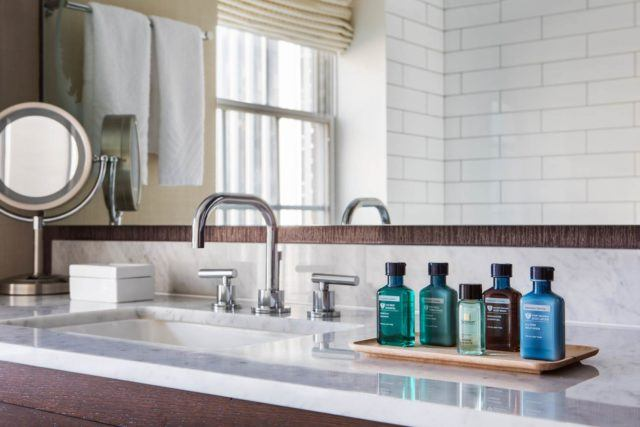 five labeled bottles on tray next to gleaming bathroom sink