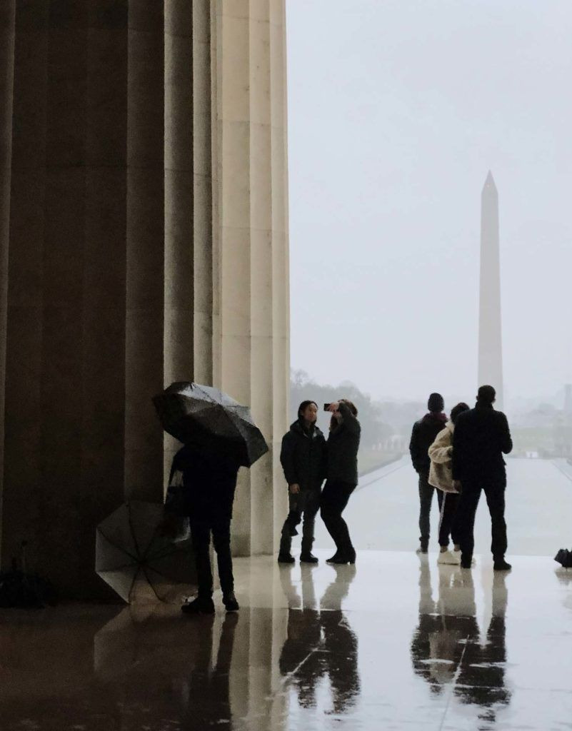 tourists looking at the Washington Monument on a rainy day