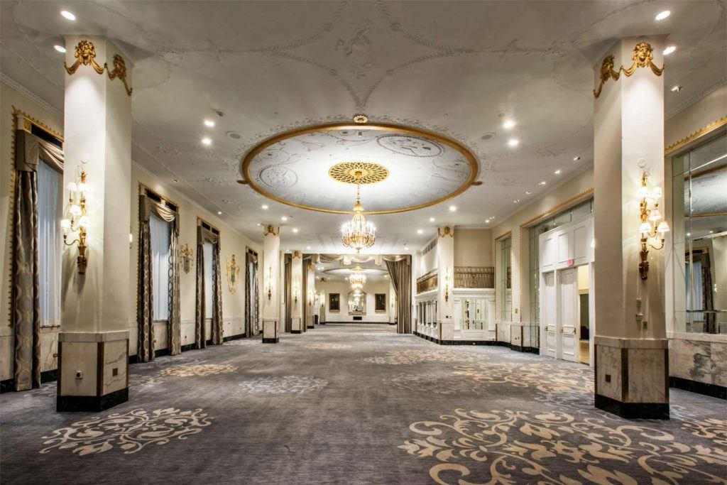 gray and brown floral carpet and large chandelier in empty ballroom venue