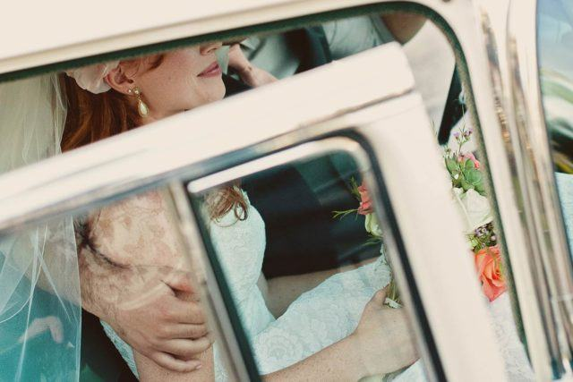 bride and groom sitting in white car