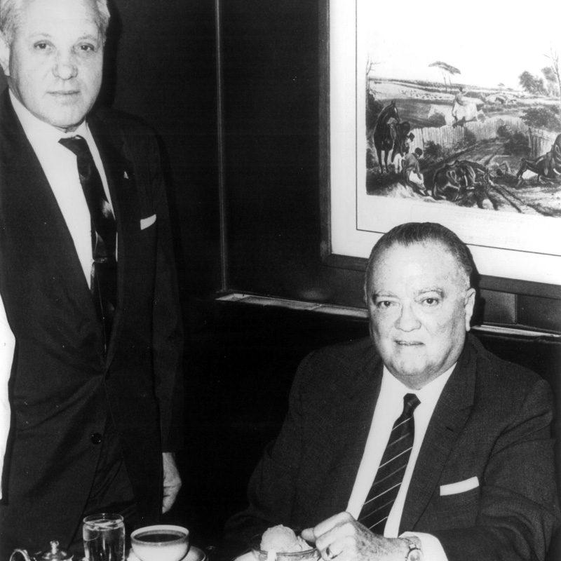man in black suit jacket beside man in black suit