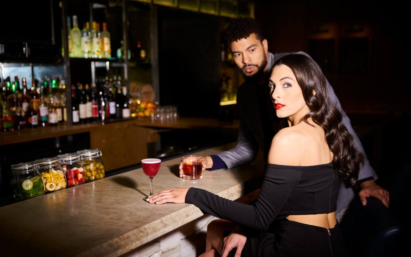 two people sitting at a bar with drinks