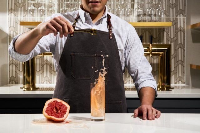 bartender making a drink at a bar next to a squeezed grapefruit
