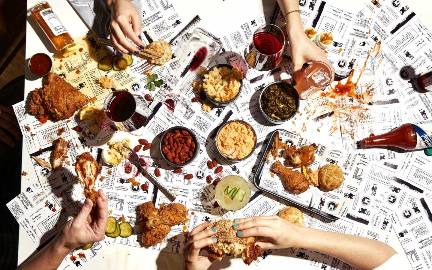 overhead of a table covered in newspaper with fried chicken dishes on it