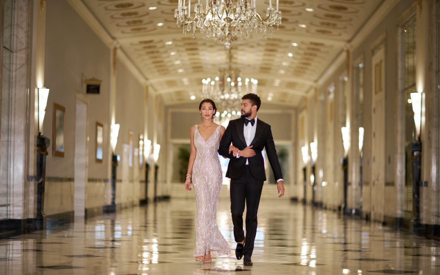 man in black suit and woman in white wedding dress walking on hallway