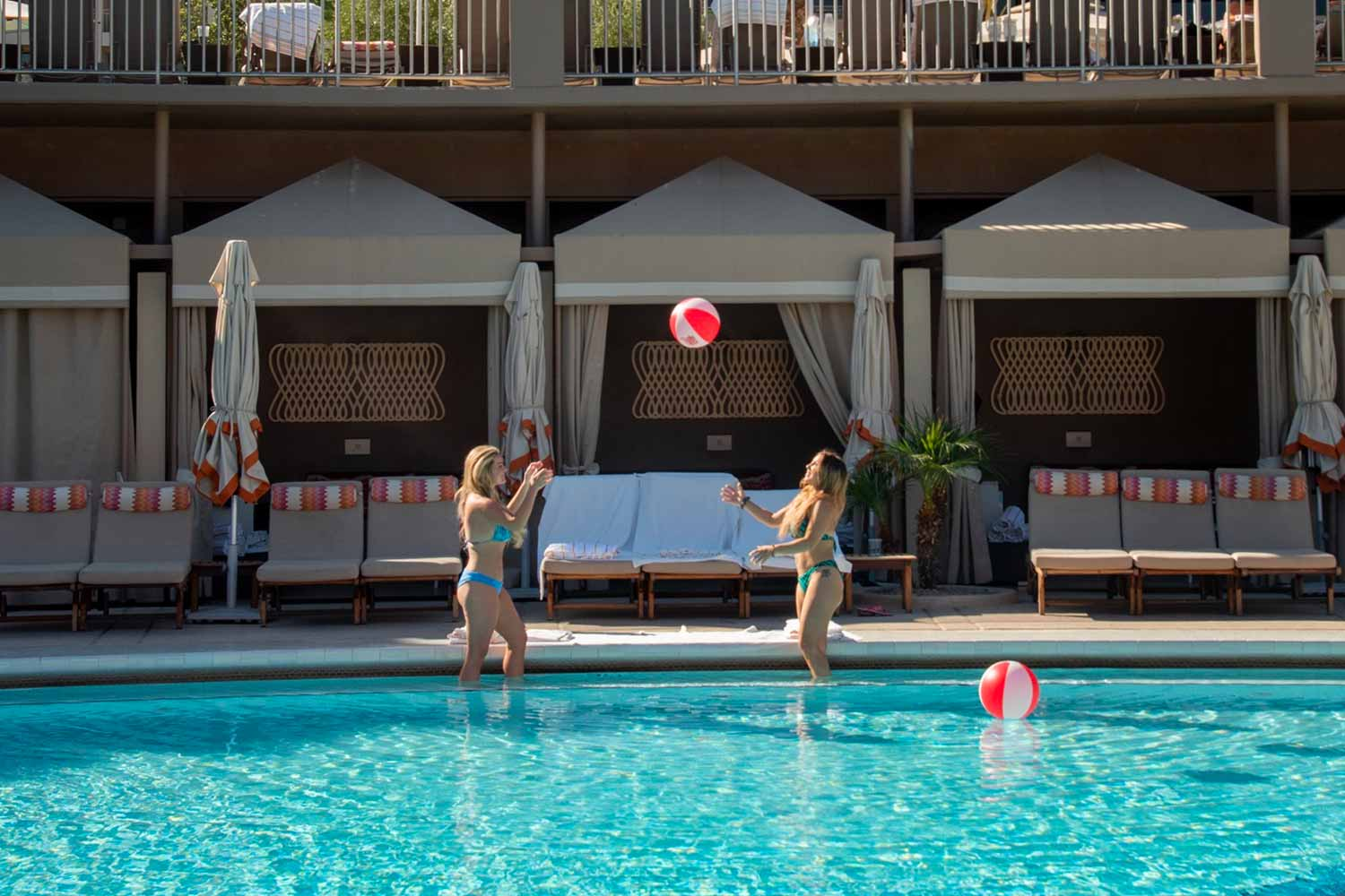 two women play with a blow up ball near pool's edge