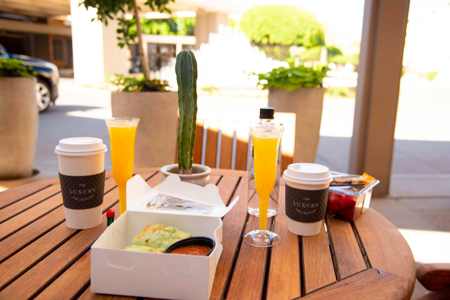 coffee, wraps, and fresh fruit to-go with tall stemmed glasses of mimosas