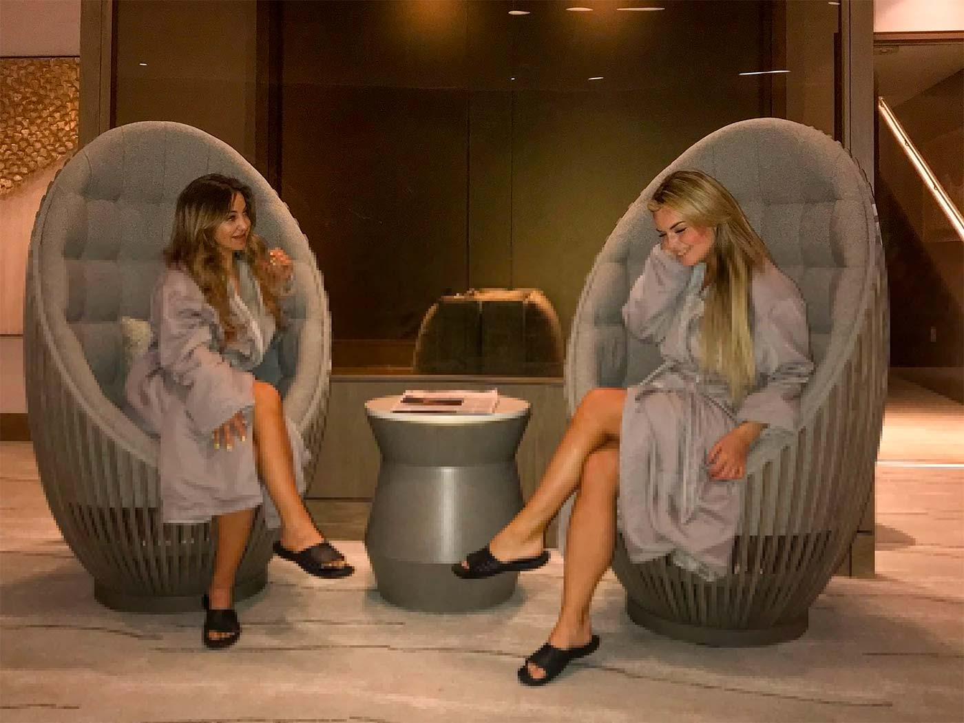 two women sit in spa armchairs while wearing robes