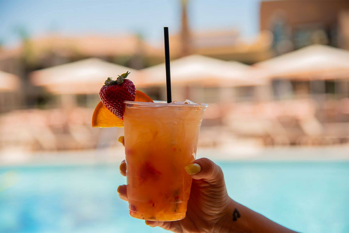 woman holding mixed drink near outdoor pool