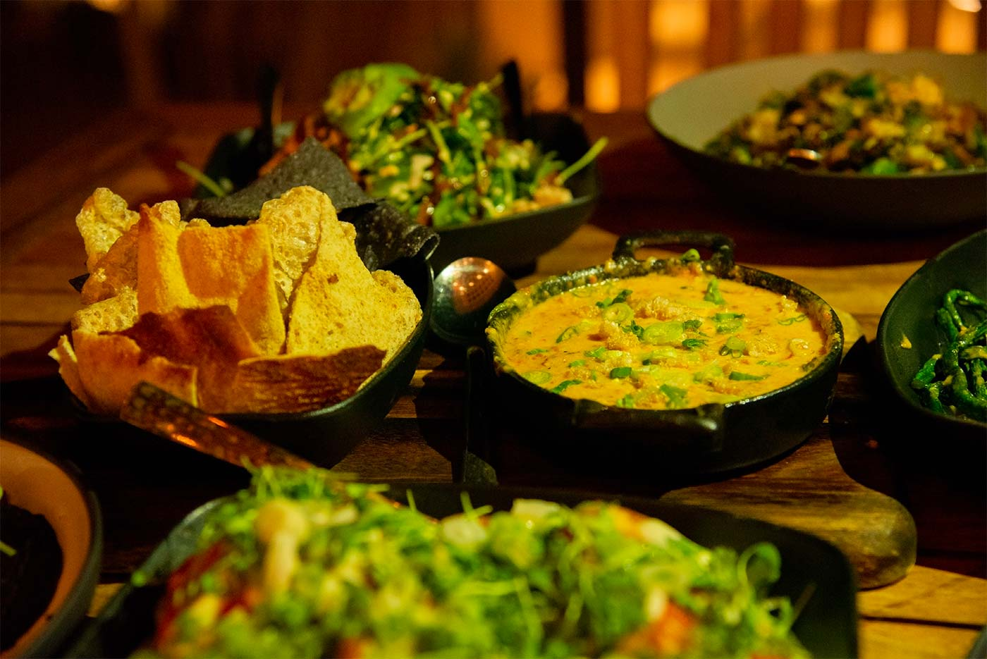 an array of Mexican food dishes on wooden table