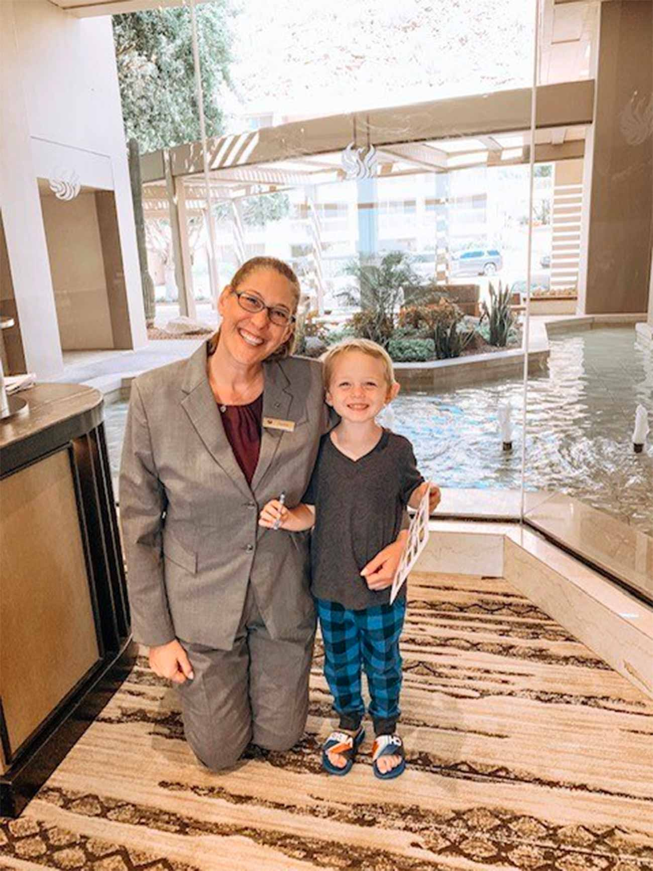 young boy smiles with hotel manager