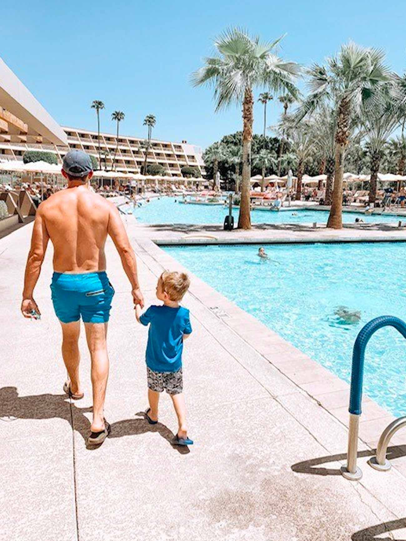 dad holds son's hand while walking near edge of outdoor pool