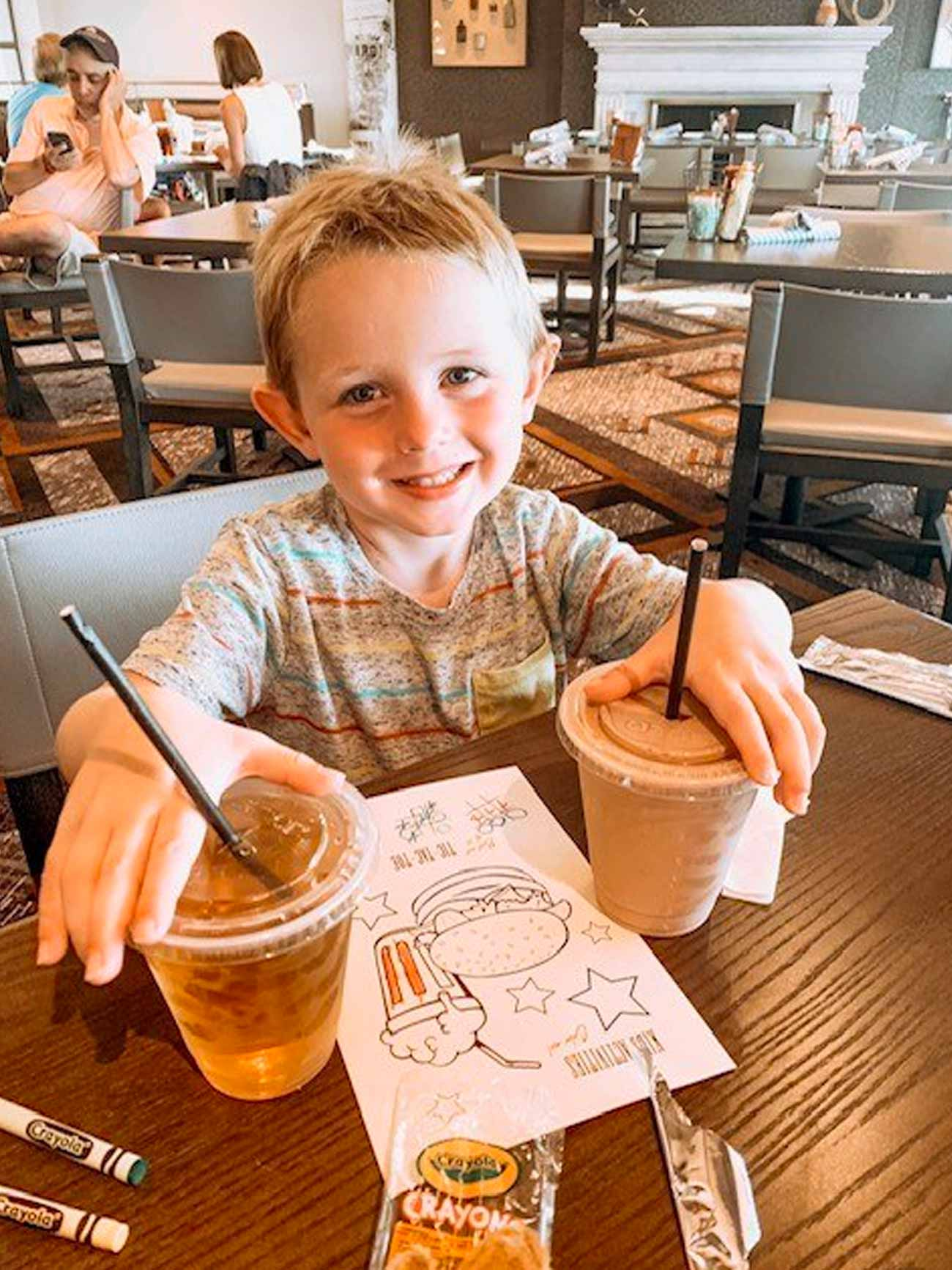 young boy holds both of his drinks at restaurant, smiling proudly