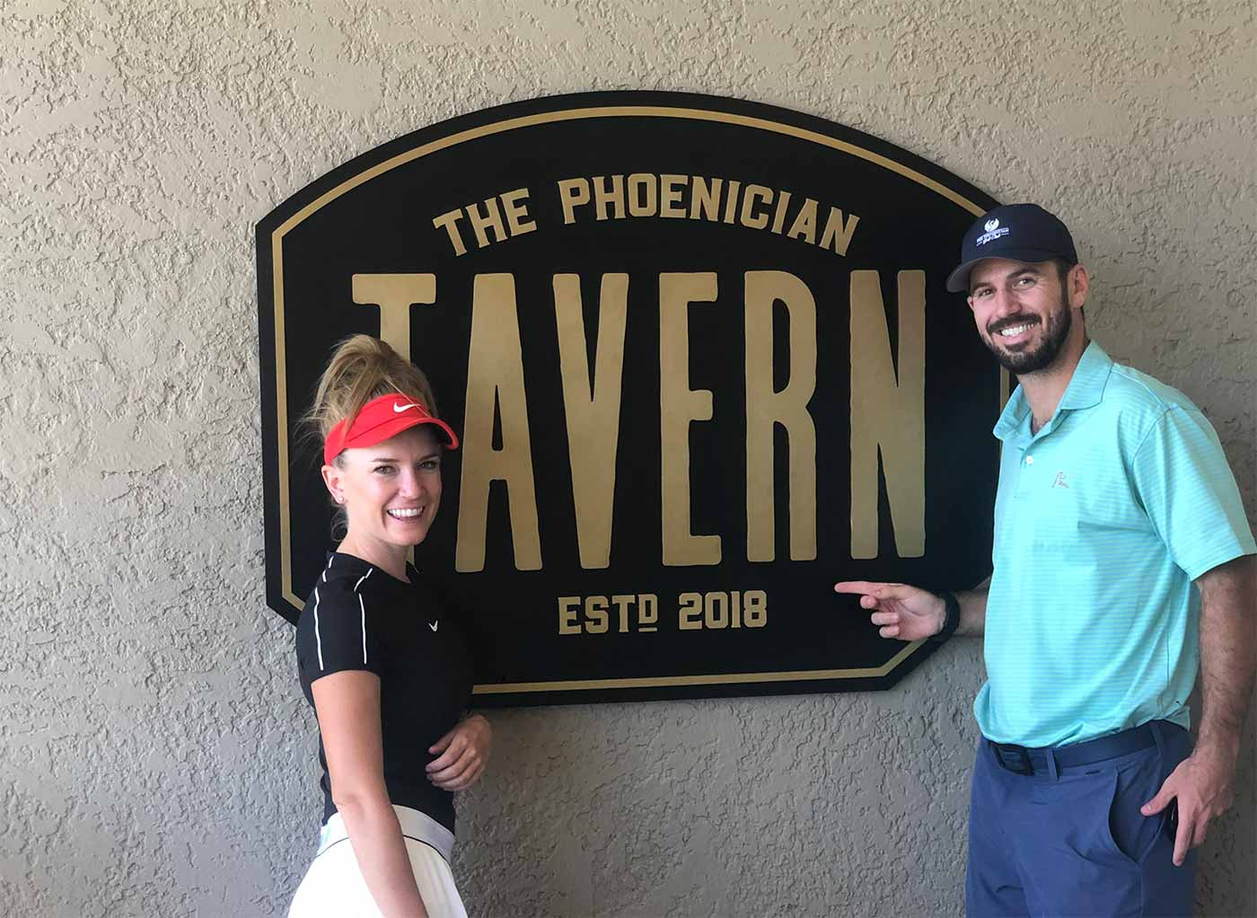 two golfers stand in front of entrance sign to The Phoenician Tavern