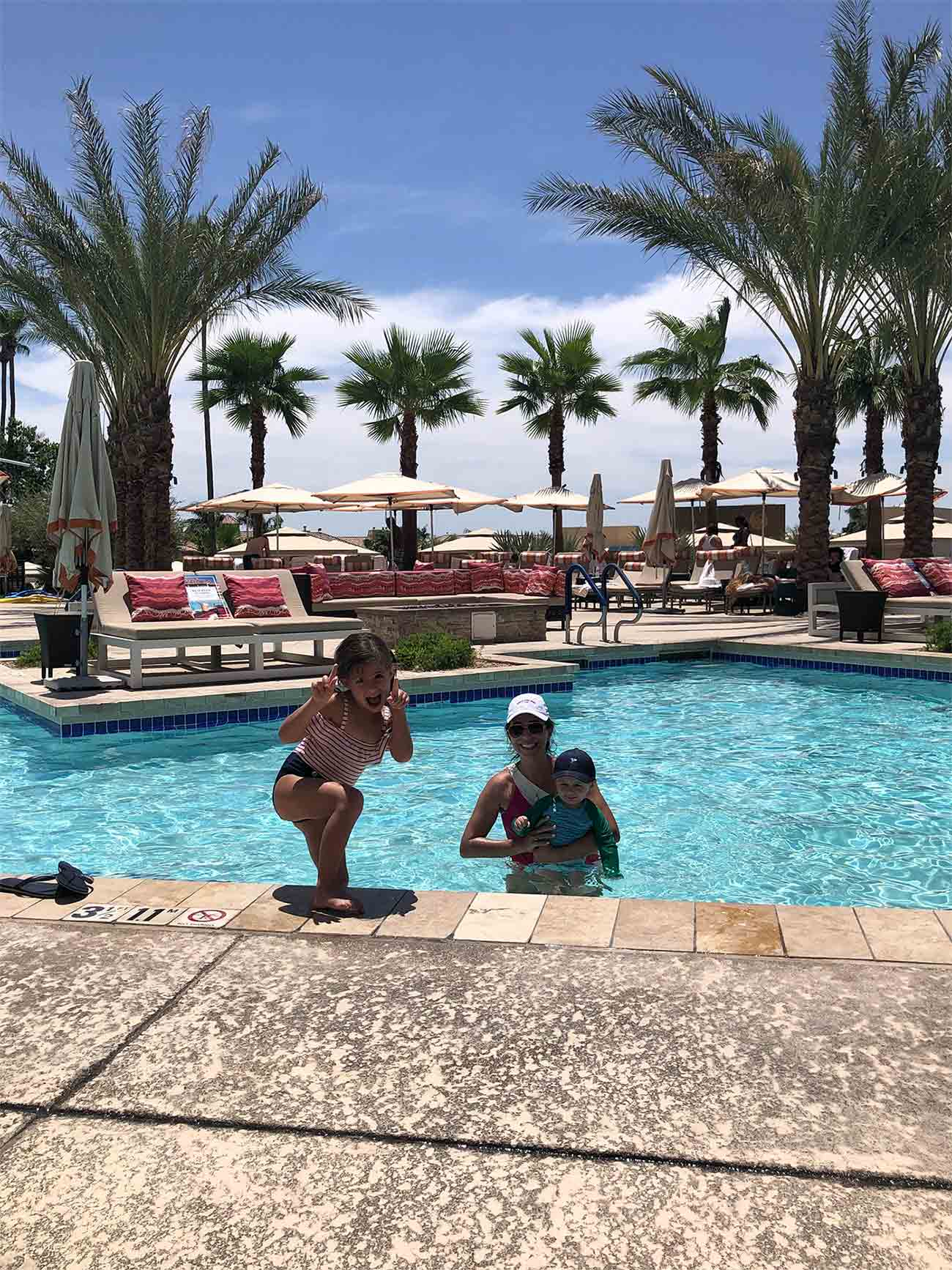 mother, young son and daughter swimming in pool