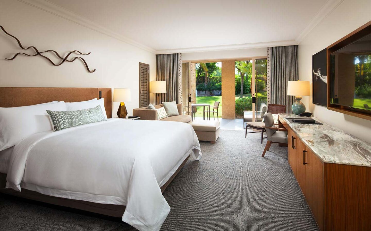 a luxury hotel room with a king size bed, sitting area, and patio doors opening to an outdoor garden